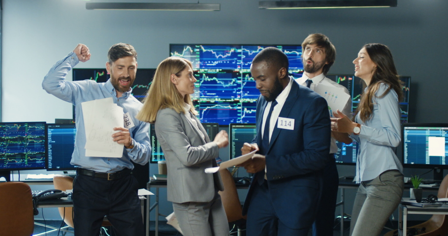 Happy funny cheerful mixed-races male and female traders dancing, having fun and tossing documents after long hard working day. Multiethnic men and women colleagues celebrating successful trading. Royalty-Free Stock Footage #1056665354