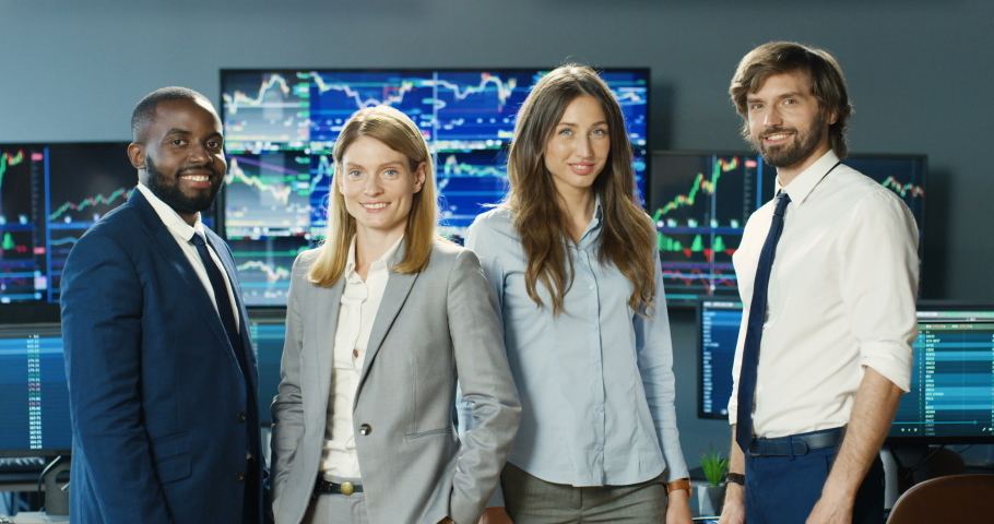 Portrait of young male and female mixed-races traders smiling to camera in stock exchange office with monitors. Multiehnic men and women investors posing in trading room. Teamwork concept. Royalty-Free Stock Footage #1056665366