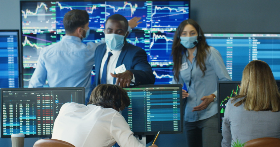 Rear of Caucasian man and woman sitting at computers and working in trading office. Multiethnic traders in medical masks talking and discussing sells and buys. African American male giving orders. Royalty-Free Stock Footage #1056665372