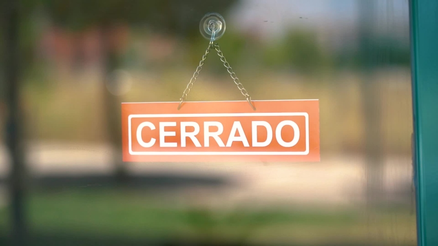 Open and close sign in spanish changed by a hand inside a glass door