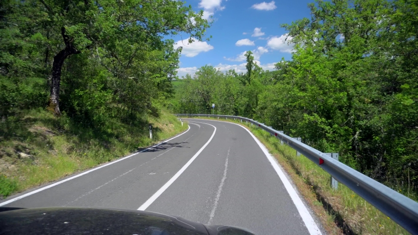 A turn on a beautiful asphalt road. Solid line on a two-way track. POV of driving travel on highway road among forest in countryside. Blue sky with white clouds White posts at the edges of the highway | Shutterstock HD Video #1056668657