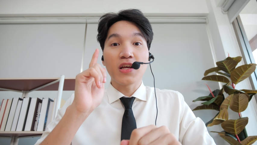 Young Asian male confident support service representative talking to web camera. Asian Businessman in headset communicates by conference video call.