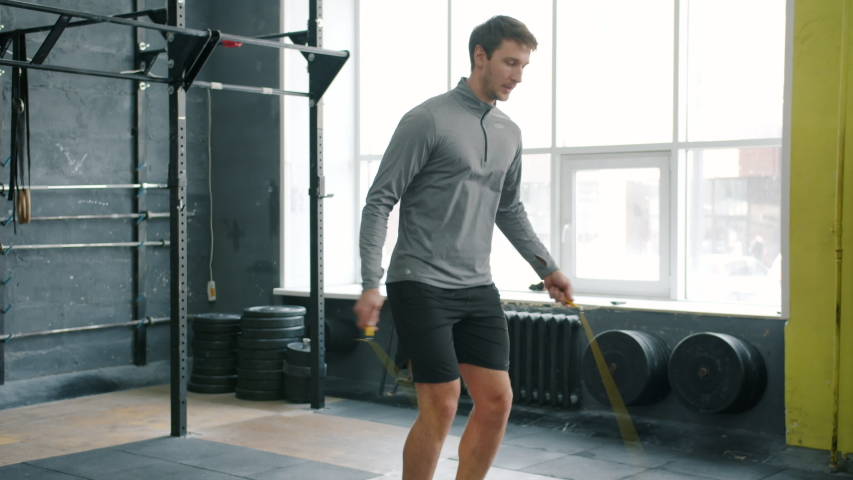 Handsome young sportsman is skipping with jumping rope indoors in gym focused on cardio exercise training alone. People, lifestyle and sports concept.