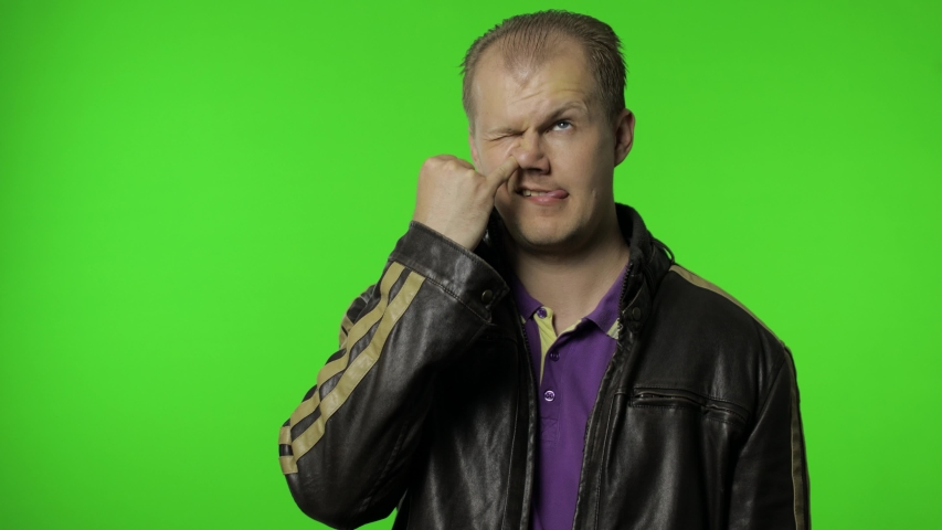 Funny stupid rocker man in jacket picking nose with silly brainless humorous expression, removing boogers, uncultured habit, bad manners. Portrait of guy biker on chroma key background