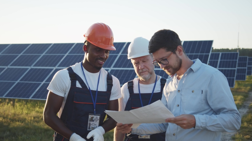 Chief engineer and multi-ethnic specialists learning the report of investment for solar plant construction. Business team. Negotiation. Clean energy. Industry. Royalty-Free Stock Footage #1056680387