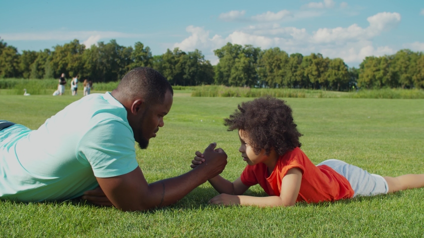 Joyful handsome african american father and playful adorable little mixed race son with curly hair arm wrestling lying on green grass in public park, enjoying playtime and leisure in summer nature.