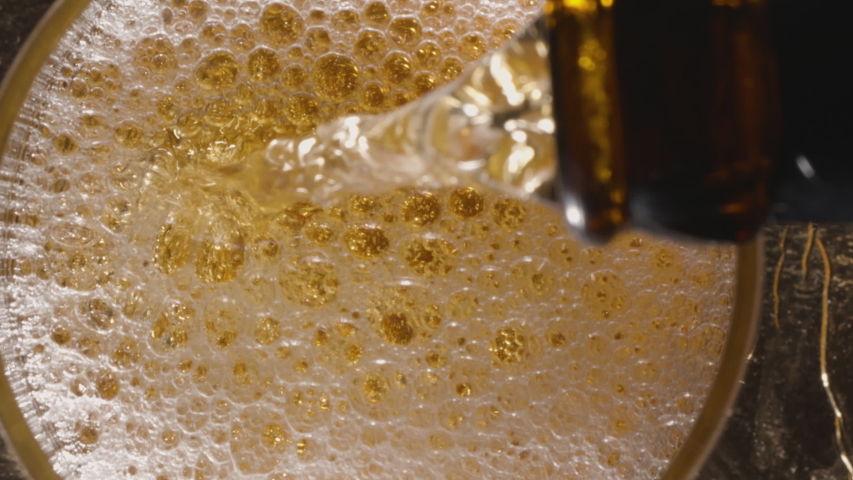 Pouring beer into a glass. View from above. A jet of beer is poured into the glass, covering the bottom with foam and raising the level to the top of the glass. | Shutterstock HD Video #1056682382