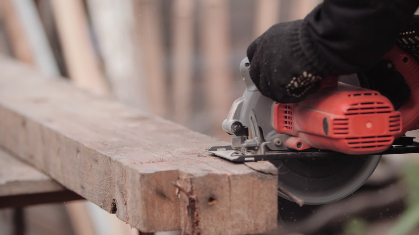 Carpenter in work clothes and gloves neatly cuts piece of board with circular electric saw and strokes wood with hand, close-up view in slow motion. Flying sawdust of working circular.  | Shutterstock HD Video #1056682652