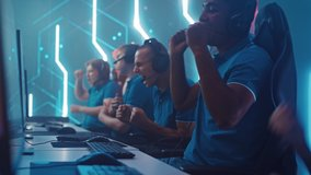 Diverse Esport Team of Pro Gamers Playing in Video Game, use Headsets to Talk, Win Championship and Celebrate with High-Five. Stylish Neon Cyber Games Arena. Online Broadcasting of Tournament Event