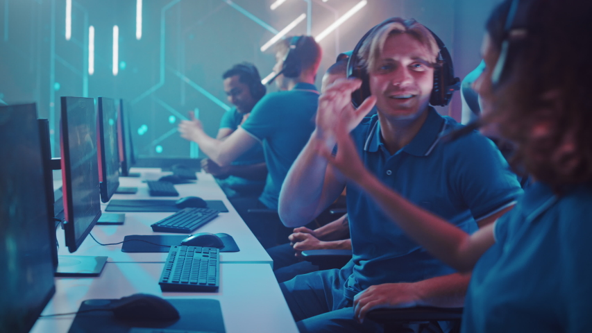Diverse Esport Team of Pro Gamers Play in Computer Video Game and Win Championship, Celebrate with High-Fives. Stylish Design Cyber Games Arena. Online Streaming of Tournament. Side View | Shutterstock HD Video #1056687302