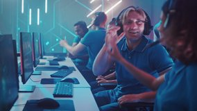 Diverse Esport Team of Pro Gamers Play in Computer Video Game and Win Championship, Celebrate with High-Fives. Stylish Design Cyber Games Arena. Online Streaming of Tournament. Side View