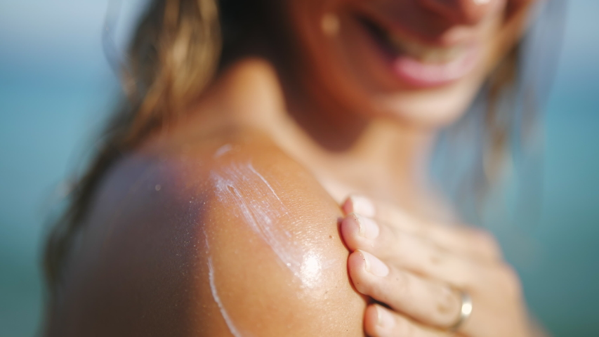 Close up of a happy smiling young woman is applying a sunscreen or sun tanning lotion on a shoulder to take care of her skin on a seaside beach during holidays vacation.