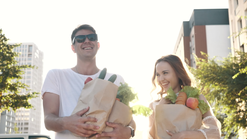 Happy Carefree Couple Laughs Walking Along Street to Home from Market, Carrying Bags with Fresh Healthy Food. Fun Grocery Shopping Together, Casual Life of Young Excited Family Enjoying Joke Outdoors Royalty-Free Stock Footage #1056688781