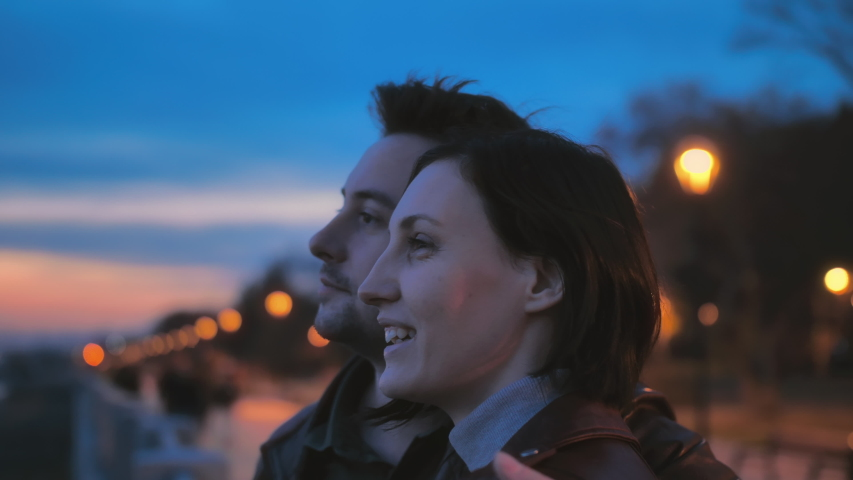 Close up portrait of a beautiful young couple at night city street at colorful lights background. A romantic atmosphere. Two Lovers hugging and admiring the sunset. Happy together.     Shutterstock HD Video #1056698930