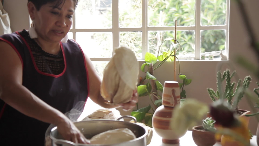 Mexican woman making authentic steamed Tamales with mole negro and Salsa verde in a humble kitchen and livingroom with olla de barro and banana leaves. With corn dough mixed with her own hands. Royalty-Free Stock Footage #1056698954