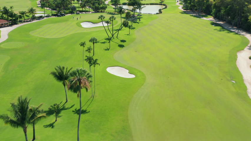 Aerial footage of people on a golf course playing the sport match in Miami, Florida, USA. Cinematic overhead view on active men playing the golf game on a sunny summer day. Background for business
