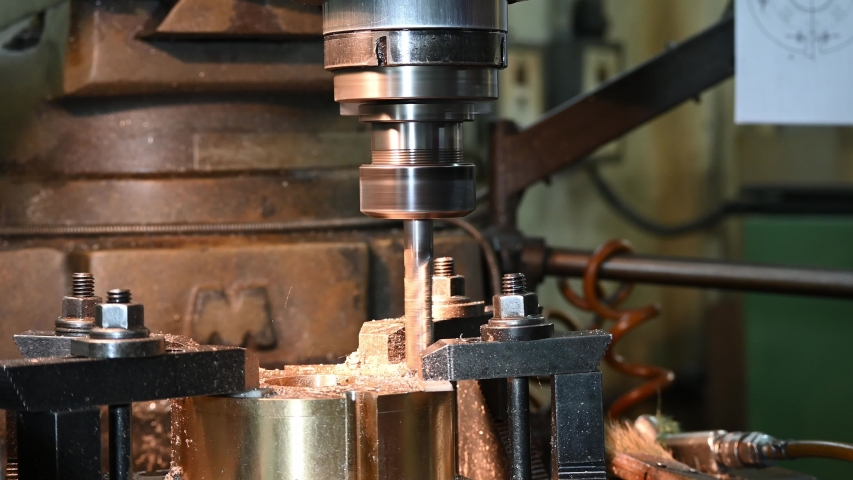 The manual milling machine plunge milling at the brass  part by solid flat end-mill tools. The metal working process by NC milling machine. Royalty-Free Stock Footage #1056701723