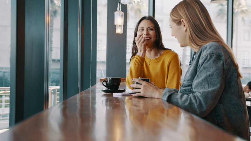 Two young women friends sitting at coffee shop having a coffee and chatting. Female friends meeting at cafe on a weekend.   Royalty-Free Stock Footage #1056702662