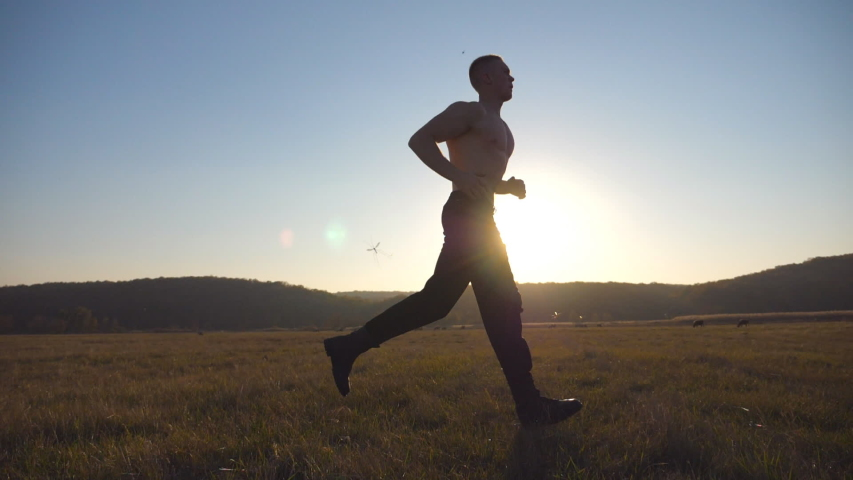 Young muscular man running through field with beautiful landscape at background. Male athlete trains in nature. Guy jogs at morning time. Unity with nature. Healthy active lifestyle. Side view Slow mo | Shutterstock HD Video #1056713684