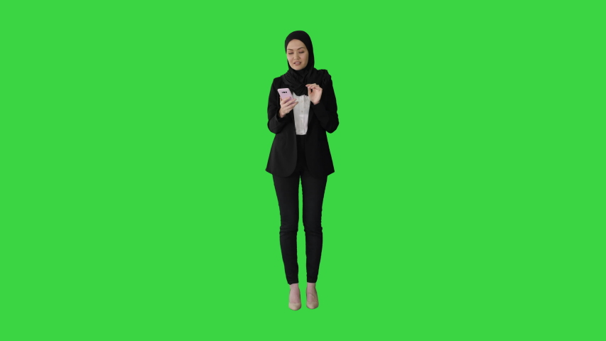 Arabic Business woman wearing hijab speaking on the phone on a Green Screen, Chroma Key.