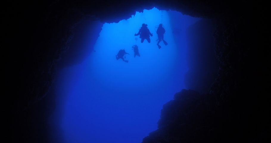 Cave diving underwater scuba divers exploring caves and having fun ocean scenery sun beams and rays background