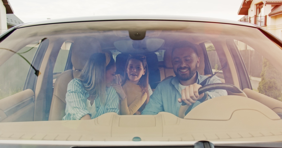 Front view of happy loving parents and their excited kids speaking smiling driving car in city. Young family traveling abroad by car in summer. Concept of lifestyle, happy family, travel together.