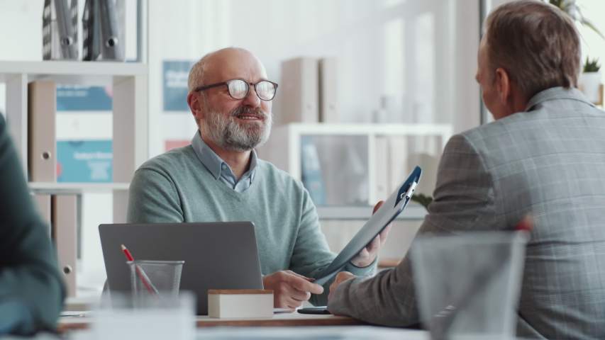 Senior male executive manager greeting colleague with handshake, checking documents in file, smiling and talking with man during office workday Royalty-Free Stock Footage #1056733859