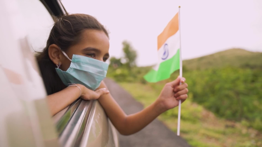 Young girl kid with a medical mask holding an Indian flag in moving car window. Concept of celebrating Independence or republic day during coronavirus or covid-19 pandemic. Royalty-Free Stock Footage #1056735158