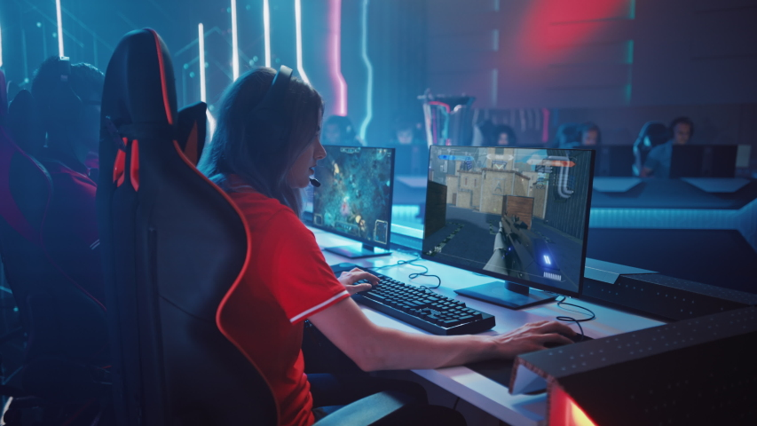 Beautiful Young Female Gamer Plays Computer Video Game FPS Shooter on a Championship. Diverse Esport Team of Play in Mock-up Video Game. Stylish Neon Cyber Games Arena. Side Arc View | Shutterstock HD Video #1056738500
