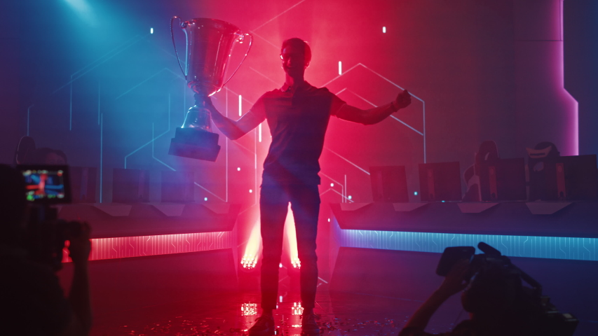 Professional Video Games Player Tournament Winner Celebrates Victory Cheering and Holding Trophy. Big Stylish Neon Bright Championship Arena doing Pro Computer Gaming Event with Online Streaming | Shutterstock HD Video #1056738506