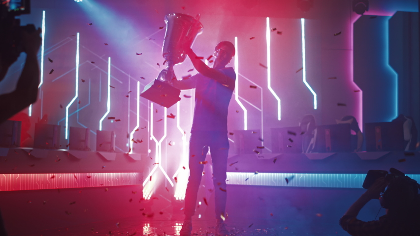 Professional Video Games Player Tournament Winner Celebrates Victory Cheering and Holding Trophy. Big Stylish Neon Bright Championship Arena doing Pro Computer Gaming Event with Online Streaming | Shutterstock HD Video #1056738512