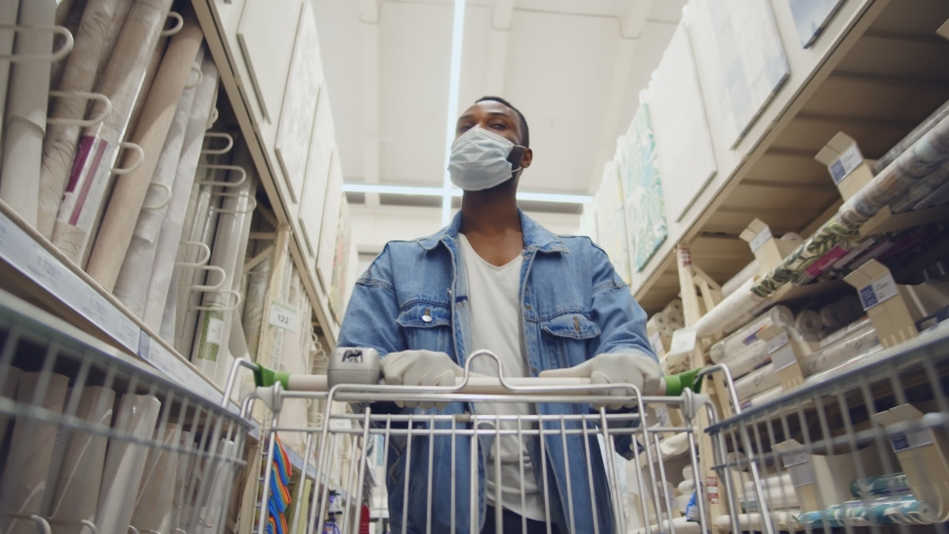 African man wearing protection facemask choosing wallpaper in hardware store. Low angle view of afro guy pushing shopping cart buying materials in house improvement store wear safety mask and gloves Royalty-Free Stock Footage #1056739022