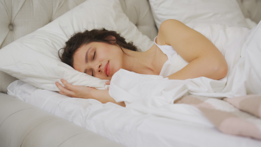 Calm young woman sleeping well in comfortable cozy fresh bed on soft pillow white linen orthopedic mattress, peaceful serene girl resting lying asleep enjoying healthy good sleep nap in the morning | Shutterstock HD Video #1056748718