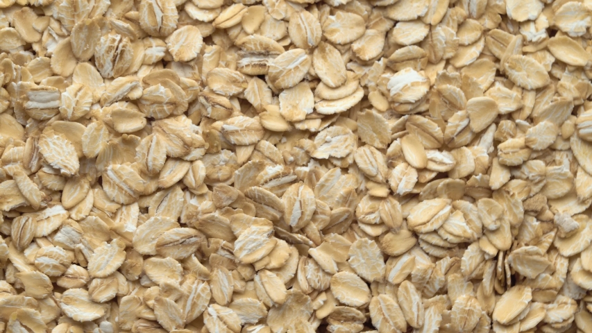Oatmeal. Oat flakes. Close-up rotating. Dry oat flakes grains background, close up rotation loopable 4k top view. Food background. Gastronomy concept, organic food. Macro rotation oat flakes. | Shutterstock HD Video #1056751427