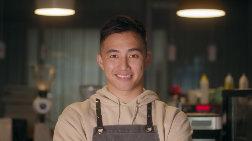 Successful small business korean owner man standing with crossed arms with employee in background preparing coffee. Portrait of asian young male cafe owner . Royalty-Free Stock Footage #1056752903