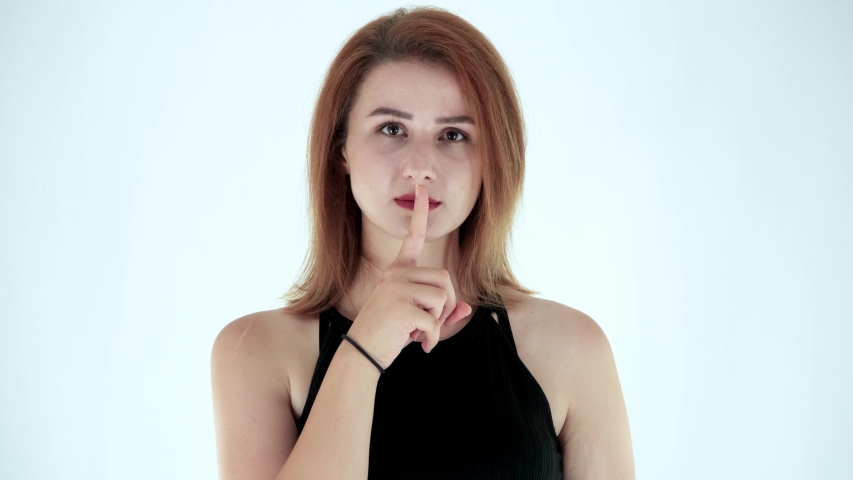 Beautiful young woman shushing, Asking to keep silence or secrecy. Studio shot, isolated on white background | Shutterstock HD Video #1056753368