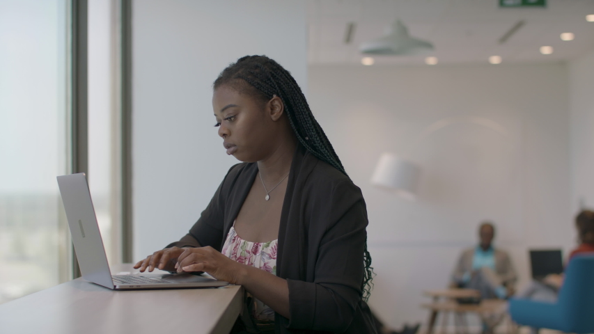 Back at work at a technology firm. A  computer programer works on her laptop. Business is back. Shot in slow-motion and in 4k.  Royalty-Free Stock Footage #1056754283