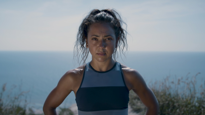 Portrait of a powerful and confident woman standing on a cliff's edge. Full of pride after achieving her goals. Shot in 4k.    Shutterstock HD Video #1056757478