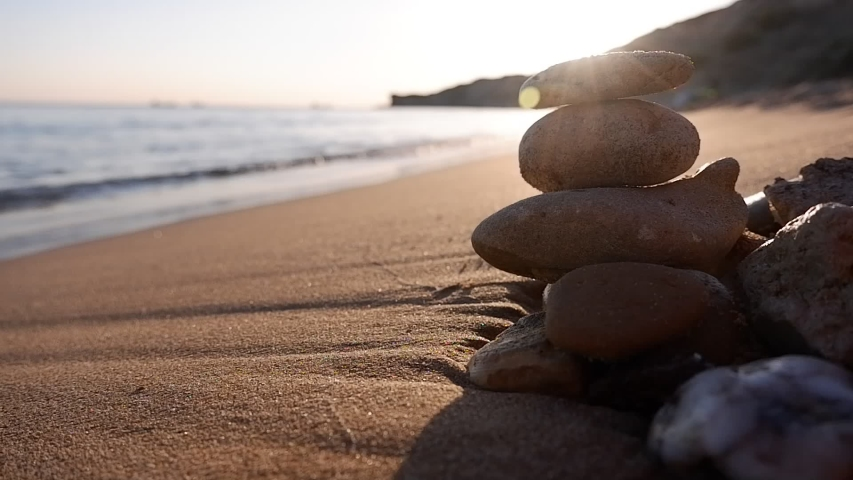 Lined sea stones in a row on the sea shore in front of the setting sun. Summer holidays, vacation and travel concept background with copy space.   Shutterstock HD Video #1056759122