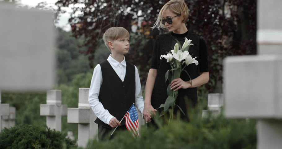 Young widow holding flower and boy with american flag looking to each other and to camera. Woman in dark clothes holding kid hand while standing at cemetery. Concept of memorial day.