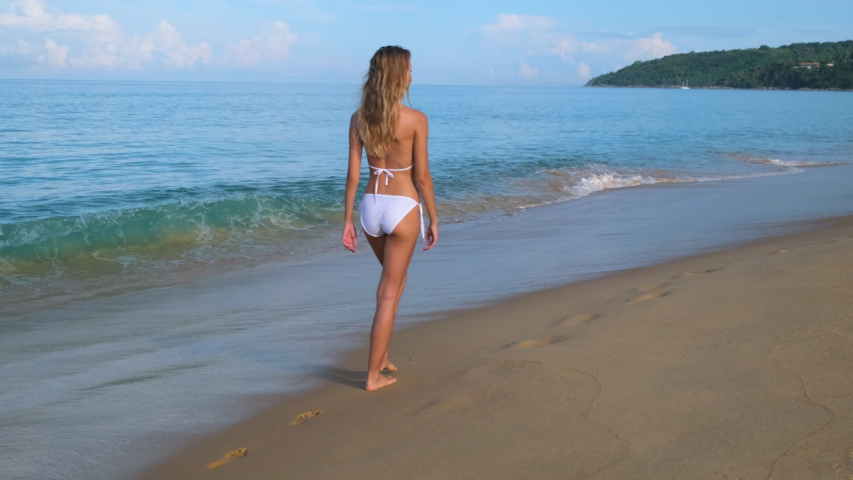 Young pretty tanned blonde sexy happy beautiful woman girl in white bikini swimsuit walking on sand tropical beach ocean, relaxing enjoying summer travel tourism relax vacation holiday. 4 K slow-mo