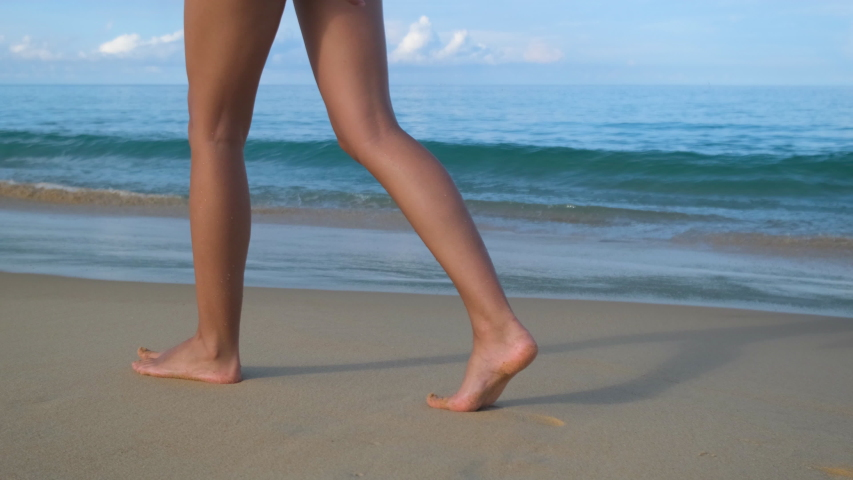 Beach travel tourist traveler woman walking barefoot on beach coastline leaving footprints in sand. Closeup of tanned female feet legs on ocean sea. wave footsteps tourism relax tropical, slow-mo 4 K Royalty-Free Stock Footage #1056767576