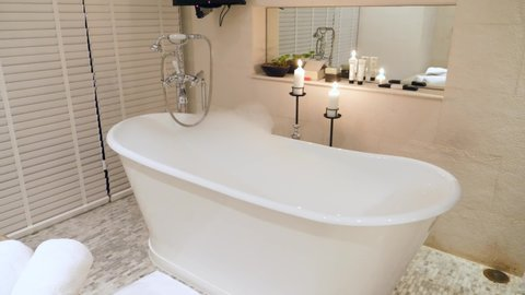 Empty Bathtub with Bubbles and Foam in Luxury Retro Style Bathroom with Candles and White Towels in the Evening, Ready for Relax and Home Spa