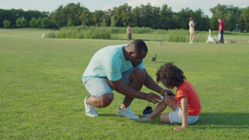 Caring loving black father with antiseptic and wet wipe providing first aid, treating and cleansing wound on sons scraped knee after fall while preschool mixed race child sitting on green field Royalty-Free Stock Footage #1056807908