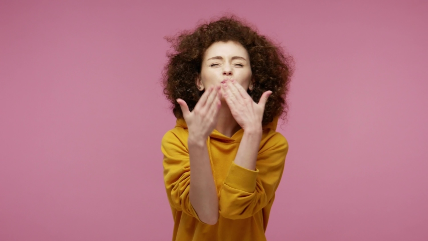 Charming carefree girl afro hairstyle in hoodie sending air kisses to camera, demonstrating love affection fondness, expressing romantic emotions. indoor studio shot isolated on pink background | Shutterstock HD Video #1056832214