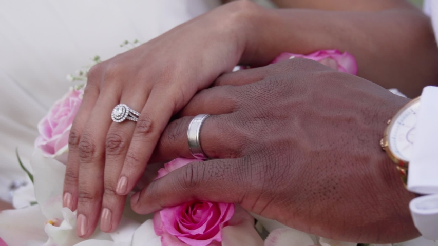 African American couple display wedding rings on top of a floral bouquet on their wedding day. Close up handheld in Maui Hawaii.