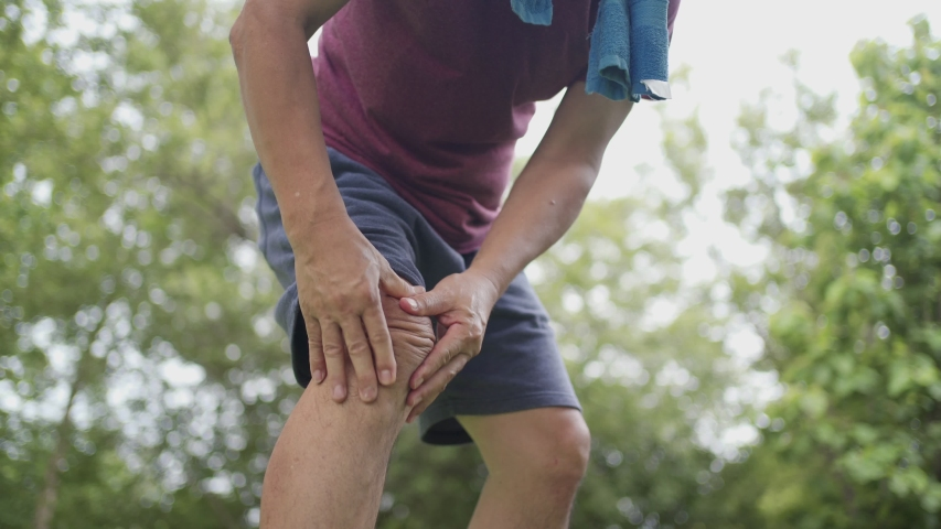 Asian tan skin male having painful knee injury during jogging exercise Inside the park with trees on the background, body condition knee pain, joint ligament problem, out door exercise knee ache Royalty-Free Stock Footage #1056842144