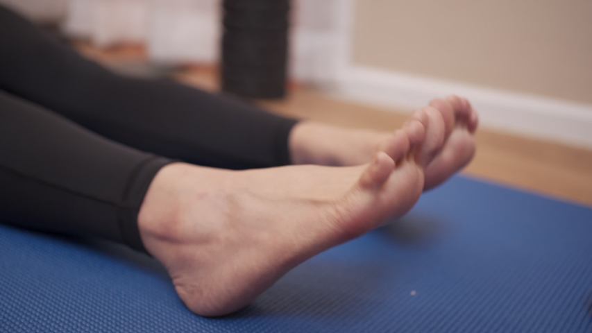 Close up female her foot, rotating ankle warming up, bone and joint stretching, sit down on exercise mat on floor, twisting ankle, flexible female sit down on exercise mat, sport injury concept   Shutterstock HD Video #1056843599