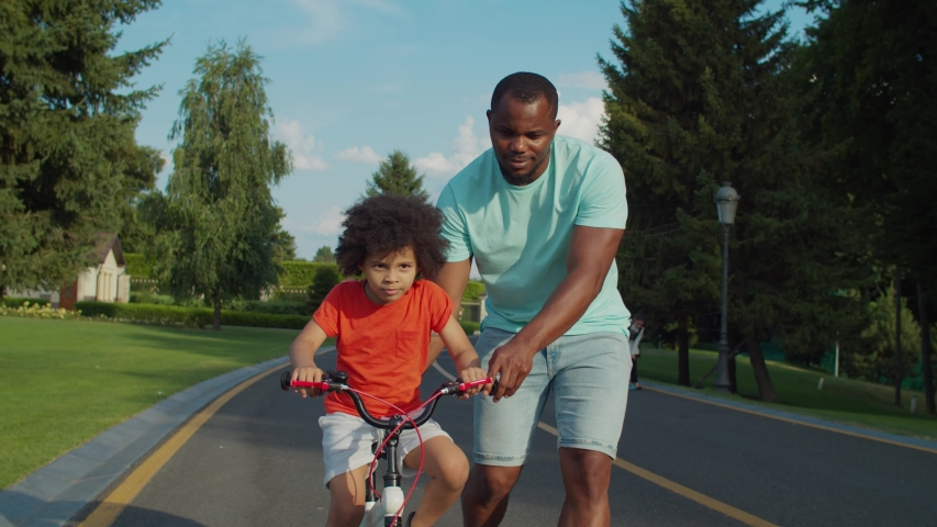 Cheerful adorable mixed race boy with curly hair learning to ride bicycle with help of caring african father on park pathway during weekend. Loving dad teaching little son to ride bike in public park | Shutterstock HD Video #1056844952