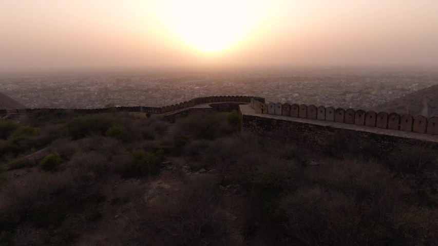 Jaipur pink city aerial panoramic. Sunset 4k footage of beautiful skyline in historic city. Woman walking in front. Birds eye view of scenic landscapes from nahargarh fort in Jaipur, Rajasthan, India